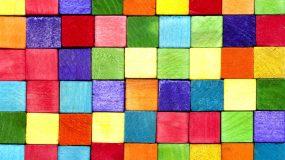 Bloquinhos quadrados de madeira empilhados um em cima do outro fazendo uma parede. Tem blocos de várias cores, azul marinho, azul claro, vermelho, rosa, laranja, amarelo, verde escuro, verde claro e vinho