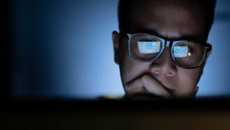 homem olha para tela do computador em sala escura