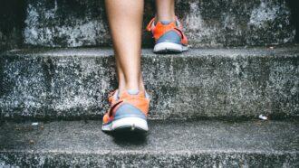 pessoa com tênis laranja sobe escada de pedra