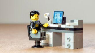 bonexo lego representando ceo sentado à mesa com computador
