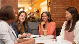 Quatro mulheres participam de uma reunião de trabalho em uma cafeteria