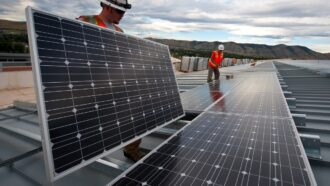 Imagem mostra homens instalando placas solares ao ar livre