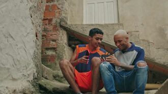 Imagem mostra dois jovens sentados em uma escada com um celular na mão